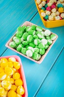 Vista laterale delle caramelle di zucchero dolci variopinte in ciotole su fondo di legno blu