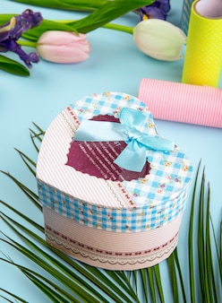 Side view of colorful tulip flowers and heart shaped gift box with rolls of adhesive tape on blue background
