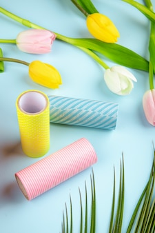 Side view of colorful tulip flowers and rolls of adhesive tape on blue background