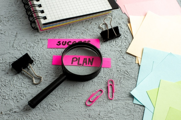 Side view of coloured envelopes and success plan writings magnifying glass spiral notebook on gray sand background
