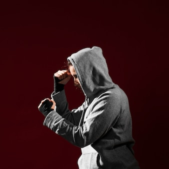 Side view combat position of a woman in hoodie