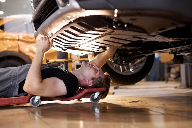 Side view on concentrated auto mechanic male working alone on the floor repairing bottom of the car