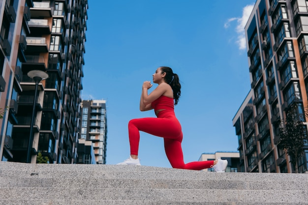 Side view of concentrating sporty caucasian woman dressed in red sportswear and white sneakers and with ponytail doing lunges.