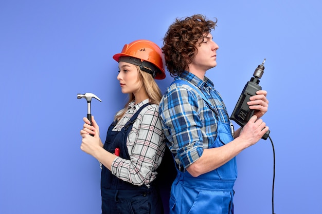 Side view on confident team of constructors builders stand back to back to each other holding tools