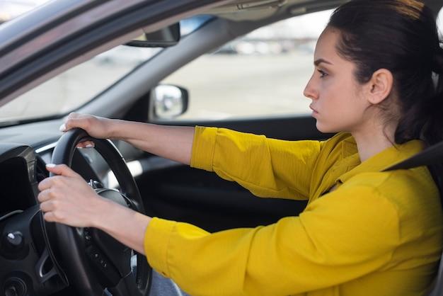 Вид сбоку уверенная женщина за рулем