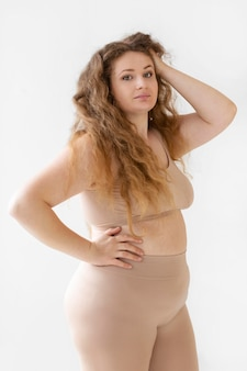 Side view of confident woman posing while wearing a body shaper