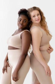 Vista laterale di donne sicure in posa mentre indossa un body shaper