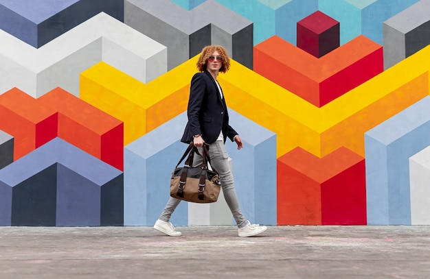Side view of confident young male with curly red hair in trendy outfit and sunglasses walking on city street, near wall with geometric graffiti and looking