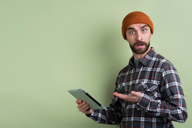 Side view of confused man holding tablet