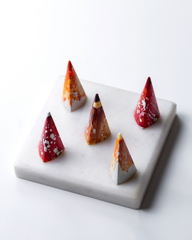 側面の円錐形のマルチ色の白いスタンドに白い斑点のあるチョコレート菓子