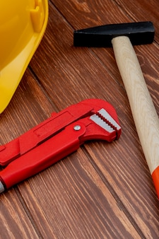 Side view of construction tools as brick hammer pipe wrench safety helmet on wooden background