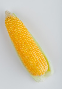 Side view of cooked corn on white surface