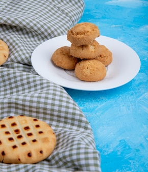 Side view of cookies on a white plate on blue