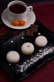 Side view of cookies with coconut flakes and chocolate on a black board served with tea
