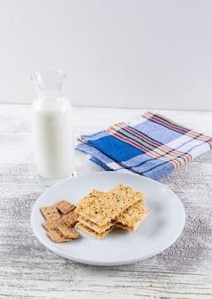 白い木製のテーブルと垂直の白い背景にミルクとサイドビュークッキー1