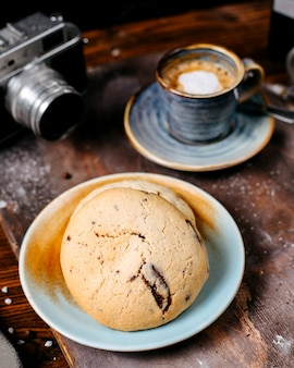 Side view of cookies with raisins served with a cup of coffee espress backgraund