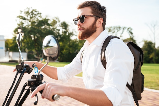 Side view of cool bearded man in sunglasses with backpack rides on modern motorbike outdoors and looking away