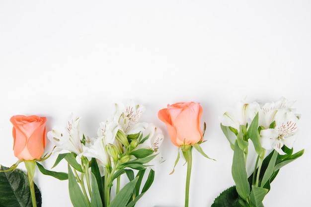 Side view of coral and white color roses and alstroemeria flowers isolated on white background with copy space