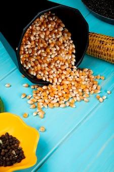 Vista laterale dei semi del cereale che si rovesciano dal vaso con i semi del pepe nero sulla tavola blu