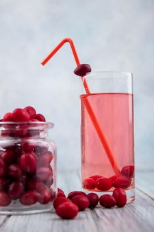 Side view of cornel juice with drinking tube in glass and jar of cornel berries on wooden surface and gray background
