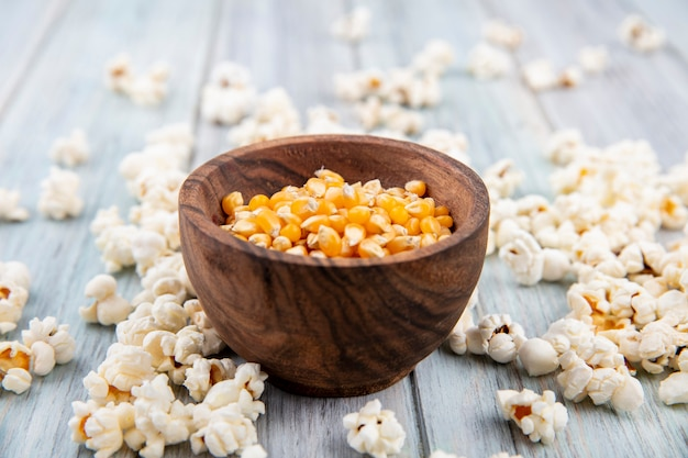 Side view of corns on a bowl with popcorn isolated on grey wooden surface