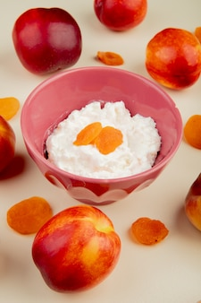 Side view of cottage cheese in a bowl and fresh sweet nectarines on white