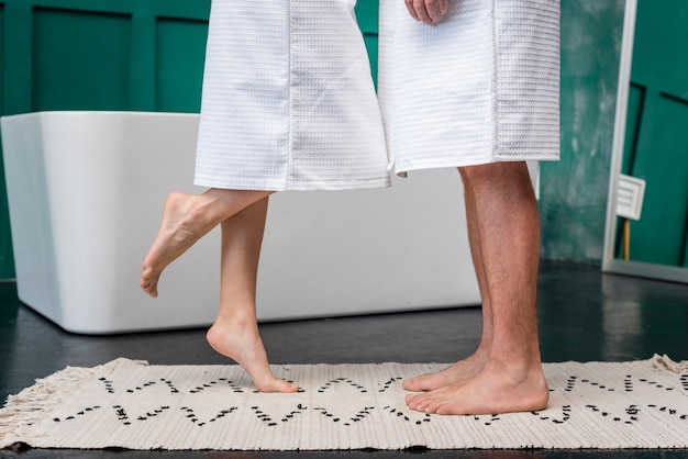 Side view of couple barefoot in bathrobes