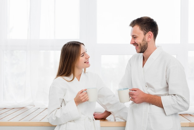 Side view of couple in bathrobes holding cups