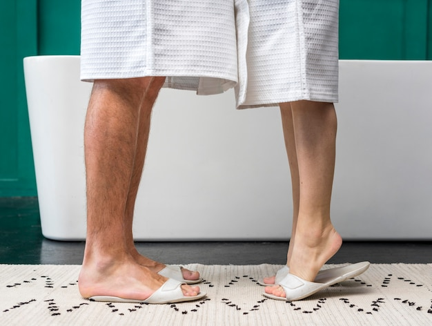 Side view of couple in bathrobes with slippers