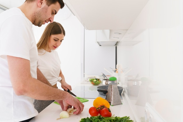Боковой вид пара готовит салат