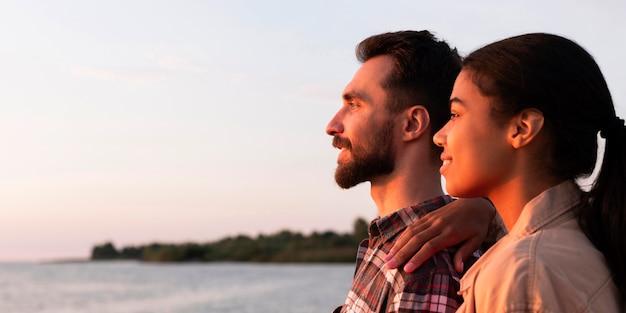 コピースペースで夕日を楽しむ側面図のカップル