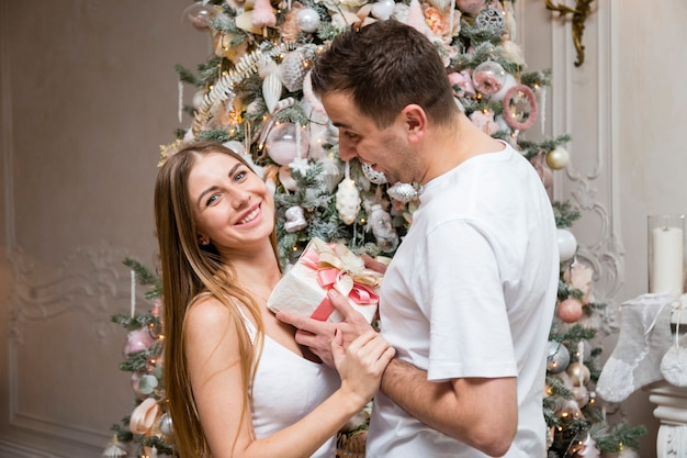 Side view of couple exchanging gift in front of christmas tree