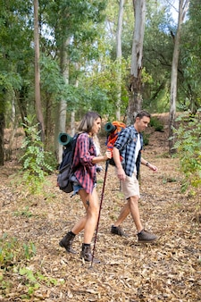 Side view of couple hiking in mountains or forest with backpacks. attractive caucasian travelers walking through path wearing boots and holding sticks. tourism, adventure and summer vacation concept
