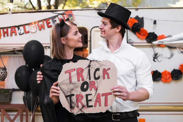 Side view couple holding halloween sign
