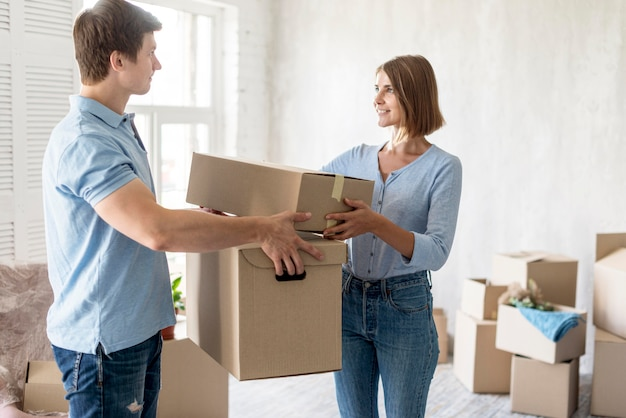 Side view of couple holding moving out boxes