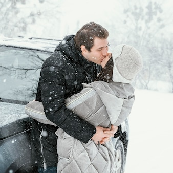 Side view of couple kissing in the snow while on a road trip