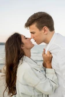 Vista laterale della coppia che si bacia mentre all'aperto