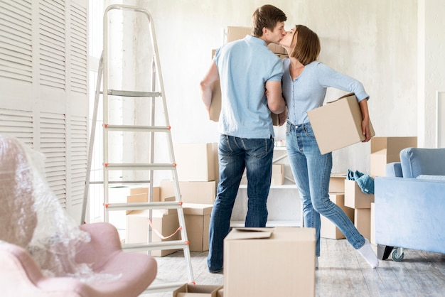 Side view of couple kissing while packing to move out