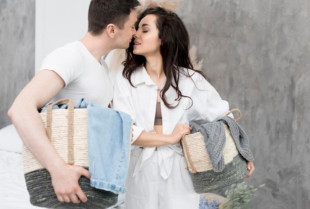 Side view of couple leaning for a kiss while holding baskets