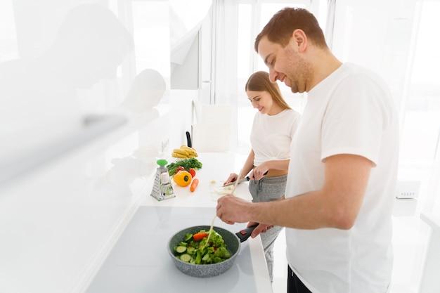 Боковой вид пара делает салат