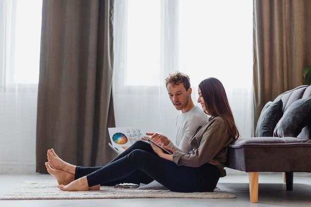 Vista laterale della coppia che intende ridipingere la casa mentre è seduto sul pavimento