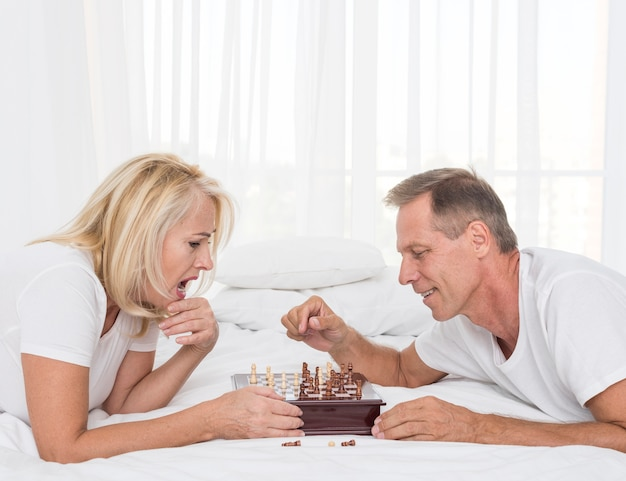 Side view couple playing chess in the bedroom