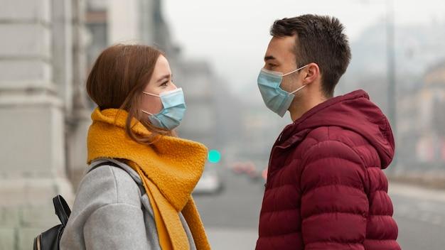 Vista laterale delle coppie che propongono insieme alle maschere mediche