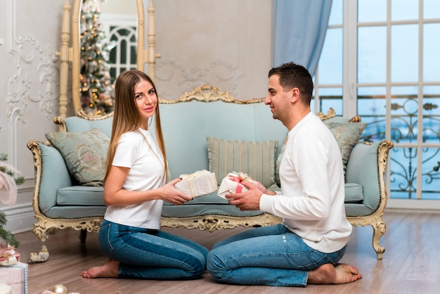 Side view of couple posing with presents in front of sofa