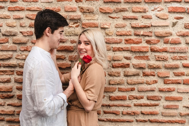 Side view of couple posing with rose and copy space