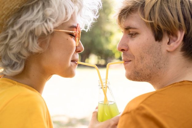 Side view of couple sharing juice bottle while in the park