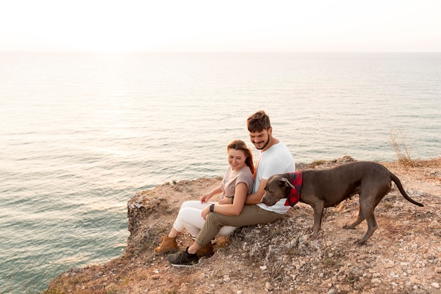 Side view couple sitting next to their dog on a coast
