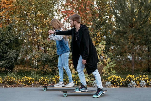 Side view of couple skateboarding together in the park