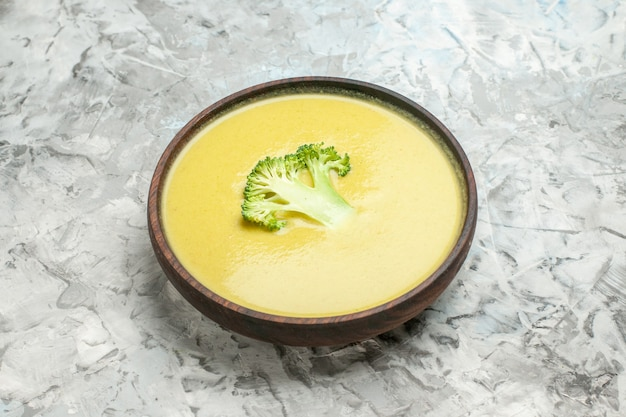 Side view of cream of broccoli soup in a brown bowl on white table