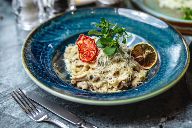 側面図クリーミーマッシュルームフェットチーネキノコソルトペッパーガーリックパスタチーズとドライトマトプレート